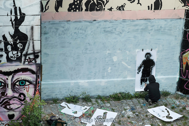 A street artist (name unknown) uses stencils to create a mural of children being attacked by a drone in the style of Banksy on a wall bordering a well-used footpath along the Danube Canal, Vienna.