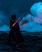Darth Vader Meets Pele: A visitor in a Darth Vader costume holds up a light saber in a show of power against power, Big Island.