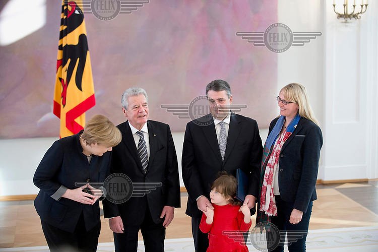 Chancellor Angela Merkel, President Joachim Gauck, and new Foreign Minister Sigmar Gabriel with his wife Anke and daughter Marie, four, pose for a photo following Gabriel's appointment at a ceremony at Schloss Bellevue Palace.