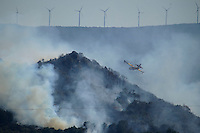 A canadair flies above smoke billowing from a forest during a wildire in Seoane de Oleiros, near Ourense, on August 25, 2013. (c) Pedro ARMESTRE
