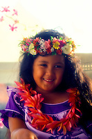 A beautiful smiling young Hawaiian girl dressed in a purple muu muu and wearing a haku lei (floral headpiece) and plumeria lei sits against a neutral background.