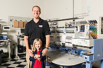 September 18, 2014. Raleigh, North Carolina.<br />  Chuck Sawyer and his daughter Elizabeth, age 6, pose for a portrait in front of the embroidery machine at his main retail and production franchise.<br />  Chuck Sawyer, 37, is the owner of three Instant Imprints franchises, specializing in promotional materials such as t-shirts,signs and mugs. Sawyer wishes he had more saved for retirement and is encouraging his none employees to start thinking about how they will save for when they get older.<br /> Publication: AARP Bulletin<br /> Editor: Jenna Isaacson-Fuller<br /> Model Released<br /> Portrait