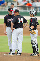 Kannapolis Intimidators relief pitcher Andrew Mitchell (45) and catcher Brett Austin (10) look on as Kannapolis Intimidators manager Pete Rose Jr. (14) makes a pitching change during the game against the Delmarva Shorebirds at CMC-NorthEast Stadium on July 3, 2014 in Kannapolis, North Carolina.  The Shorebirds defeated the Intimidators 6-5. (Brian Westerholt/Four Seam Images)