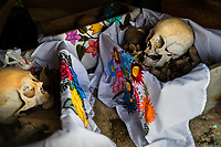 """Dried-up sculls and bones are seen wrapped in embroidered cloths and placed in wooden crates inside a niche at the cemetery in Pomuch, Mexico, 26 October 2019. Every year on the Day of the Dead, people of Pomuch, a small Mayan community in the south of Mexico, visit the cemetery to take part in a pre-Hispanic tradition of cleaning of bones of their departed relatives (""""Limpia de huesos""""). People who die in Pomuch are firstly buried for three years in an above-ground tomb then the dried-up bodies are taken out, bones are separated, wrapped in a decorated cloth, put into a wooden crate, and placed on display among flowers for veneration."""