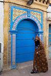 Marokko, Region Marrakesch-Tensift-El Haouz, Essaouira an der Atlantikkueste: verschleierte Frau vor einer marokkanischen Tuer in der Medina (Altstadt) | Morocco, Region Marrakesh-Tensift-El Haouz, Essaouira at the Atlantic Coast: Moroccan door in the medina