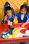 Education Preschool 3-4 year olds water table a boy and a girl wearing smocks playing together vertical