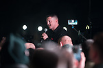 """© Joel Goodman - 07973 332324. 03/11/2017 . Manchester , UK . TOMMY ROBINSON (real name Stephen Yaxley-Lennon ) speaks to supporters at the launch of the former EDL leader's book """" Mohammed's Koran """" at Castlefield Bowl . Originally planned as a ticket-only event at Bowlers Exhibition Centre , the launch was moved at short notice to a public location in the city . Photo credit : Joel Goodman"""