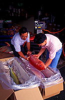 Chef Roy Yamaguchi helps pack fish with Neal Aoki of Tropic Fish Hawaii in Honolulu