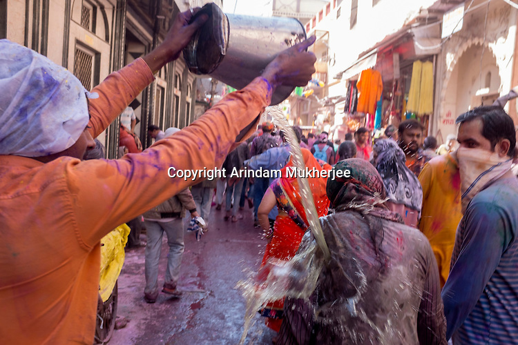 A boy put a full bucket of water on a lady on the occassion of Holi in Vrindavan. Holi - The  Hindu festival of colour is celibrated for a week in the Brraj region of Uttar Pradesh, India.
