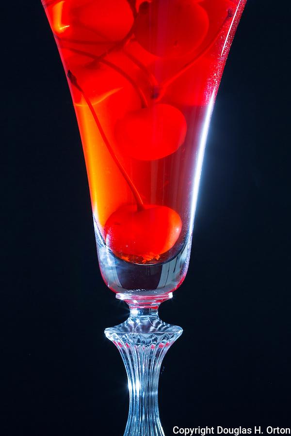 Maraschino Cherries in vintage desert glass.  Black background.