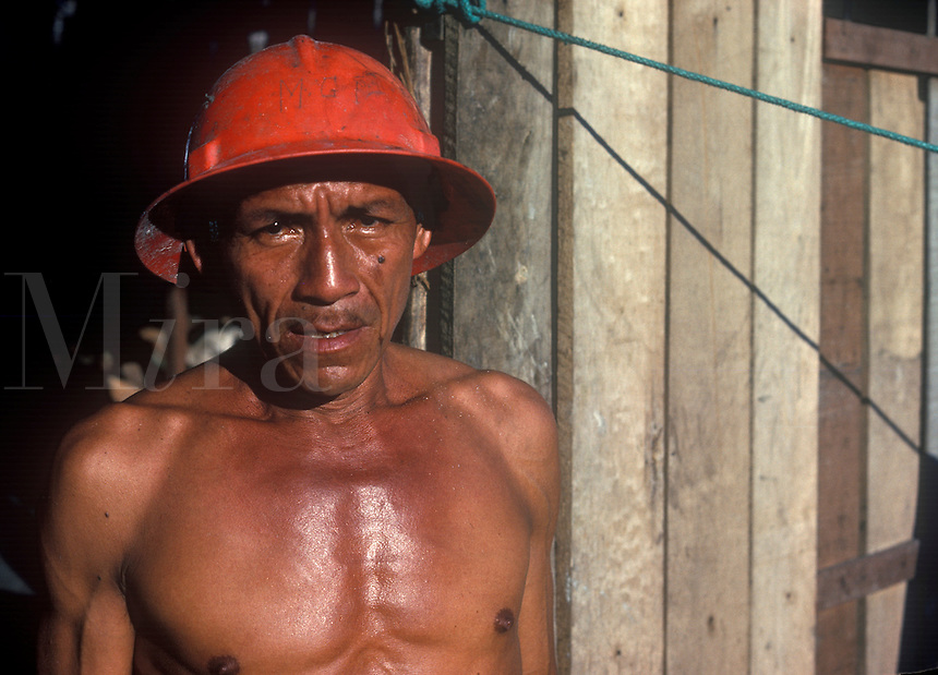 Portriat of Peruvian man from the jungle region wearing a safety hat at work.