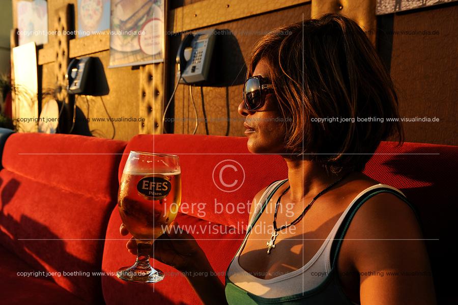 TURKEY Istanbul, woman drinks turkish Efes beer in Pub under bridge over Golden Horn/ TUERKEI Istanbul, Frau trinkt Efes Bier