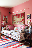 The walls of the colourful den are painted in Indian pink and the room is furnished with a crewel work sofa