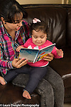 12 month old baby girl sitting with mother read to