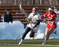 Boston College midfielder Kate McCarthy (20) on the attack as Boston University midfielder Sofia Robins (24) closes..Boston College (white) defeated Boston University (red), 12-9, on the Newton Campus Lacrosse Field at Boston College, on March 20, 2013.