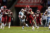 RALEIGH, NC - NOVEMBER 30: Payton Wilson #11 of North Carolina State University tackles Michael Carter #8 of the University of North Carolina during a game between North Carolina and North Carolina State at Carter-Finley Stadium on November 30, 2019 in Raleigh, North Carolina.