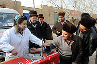CHINA province Xinjiang, market day in uighur village Langar near Kashgar, health check / CHINA Provinz Xinjiang, Blutdruckmessung, Gesundheitscheck auf Markttag in Langar einem uigurischen Dorf bei Stadt Kashgar hier lebt das Turkvolk der Uiguren, das sich zum Islam bekennt