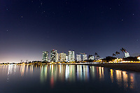 A view of buildings and cranes at night with their lights reflected on the ocean, Ala Moana Beach Park, Honolulu, O'ahu.