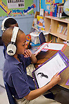Black seven year old boy in classroom listens to story on headphones and holds paper copy of story