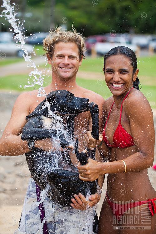 A local couple and rinsing their dog under the shower at Waimea Bay Beach Park