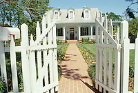 Front gate opens to brick sidewalk to traditional white clapboard home