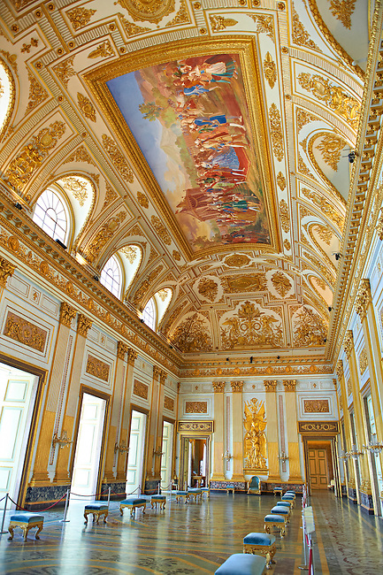 """""""The Throne Room""""  is nearly 40 meters long and was completed in 1845. On the back wall is placed a portable guilder throne. The decorations symbolise absolute power. The architrave in the room is decorated with portraits of the sovereigns of Naples stating with Roger the  Norman ending with Ferdinand II of Bourbon.   The Bourbon Kings of Naples Royal Palace of Caserta, Italy."""