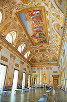 """The Throne Room""  is nearly 40 meters long and was completed in 1845. On the back wall is placed a portable guilder throne. The decorations symbolise absolute power. The architrave in the room is decorated with portraits of the sovereigns of Naples stating with Roger the  Norman ending with Ferdinand II of Bourbon.   The Bourbon Kings of Naples Royal Palace of Caserta, Italy."