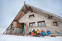 A ski tour through the Pirin Mountains of Bulgaria. Skiers relaxing outside the Tevno Ezero Hut.