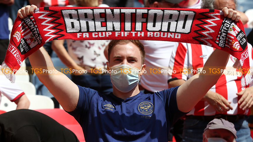 A Brentford fan proudly holds up his FA Cup 5th Round scarf. Very soon he'll be able to purchase one showing Brentford in the Premier League during Brentford vs Swansea City, Sky Bet EFL Championship Play-Off Final Football at Wembley Stadium on 29th May 2021