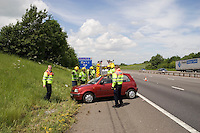 Highways Agency officers assist a car that rolled onto the embankment M40..This image may only be used to portray the subject in a positive manner..©shoutpictures.com..john@shoutpictures.com