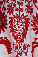 Detail of red heart embroidered onto rough linen