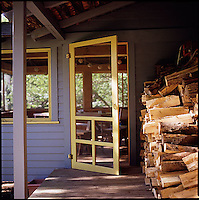 Stacked firewood next to partially opened door<br />