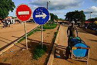 BURKINA FASO, Province Poni, Gaoua, road with red and blue traffic signs, man transport water tank / rot und blau Verkehssschilder Einbahnstrasse, Wassertransport