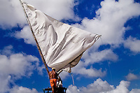 Brazilian fishermen (jangadeiros) attach the sail to the mast before putting out to sea on the beach of Prainha, Ceará state, northeastern Brazil, 8 March 2004. Jangadeiros, working on a unique wooden raft boat called jangada, keep the tradition of artisan fishing for more than four hundred years. However, being a fisherman on jangada is highly dangerous job. Jangadeiros spend up to several days on high-sea, sailing tens of kilometres far from the coast, with no navigation on board. In the last two decades jangadeiros have been facing up the pressure from motorized vessels which use modern, effective (and environmentally destructive) fishing methods. Every time jangadeiros come back from the sea with less fish.