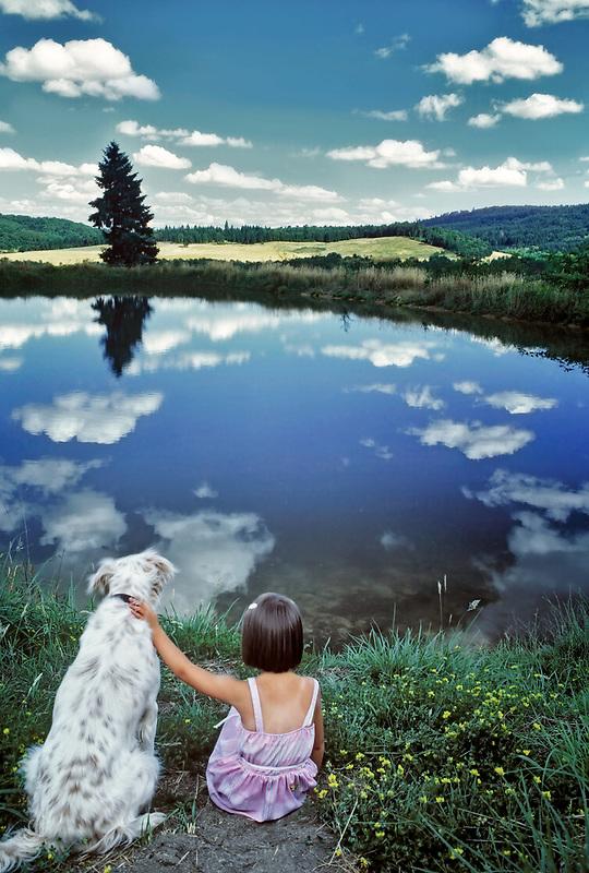 Young girl and dog at pondside. Near Monroe, Oregon.