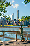 Woman at the Long Island Gantry Plaza State Park, looking across the East River at Roosevelt Island and the Manhattan skyline