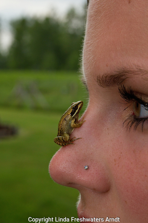 Young woman with a frog on her face