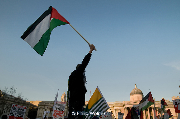 A demonstrator waves a Palestinian flag at a rally in Trafalgar Square following a march called by the Palestine Solidarity Campaign, Stop the War Coalition, British Muslim Initiative and other organisations, to protest at the Israeli bombing of Gaza.