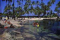 Tourists on the beach at Puu Honua O Honaunau (City of Refuge) on the Kona Coast of the Big Island of Hawaii.