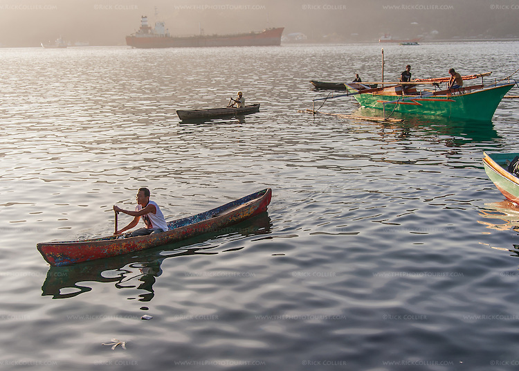 Local villagers and small fishermen maneuver in small boats every morning at the fish market in Bitung, North Sulawesi, Indonesia.
