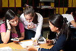 Education high school female teacher helping students with mathmatics problem nearby student holding calculator