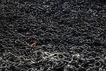 Un hombre trabaja las montañas de neumáticos que forman una inmensa mancha negra de 9,8 hectáreas (unos 10 campos de fútbol) entre el municipio de Seseña (Toledo) y Valdemoro (Madrid), a la altura del kilómetro 33,500 de la carretera de Andalucía y a unos 400 metros de una gran urbanización. Centro de almacenamiento de neumáticos de seseña, cerca de Madrid. 17 Junio 2009. (c)Pedro ARMESTRE