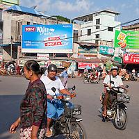 Myanmar, Burma, Mandalay.  Motorbike Traffic at an Intersection.