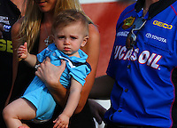 Sept. 1, 2014; Clermont, IN, USA; Katie Lucas wife of NHRA top fuel dragster driver Morgan Lucas holds son Hunter Lucas during the US Nationals at Lucas Oil Raceway. Mandatory Credit: Mark J. Rebilas-USA TODAY Sports