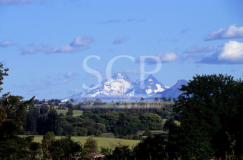Southern Chile. Snow capped volcanoes with green fields.