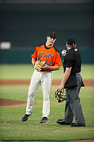AZL Giants starting pitcher Seth Corry (63) receives a clean baseball from home plate umpire West Hyer during a game against the AZL Rangers on August 22 at Scottsdale Stadium in Scottsdale, Arizona. AZL Rangers defeated the AZL Giants 7-5. (Zachary Lucy/Four Seam Images via AP Images)
