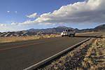 Silver SUV car on highway exiting Great Sand Dunes National Park, Colorado. John offers private photo trips to Great Sand Dunes National Park and all of Colorado. All year long.