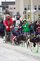 Jason Mackey and team leave the ceremonial start line with an Iditarider at 4th Avenue and D street in downtown Anchorage, Alaska during the 2015 Iditarod race. Photo by Jim Kohl/IditarodPhotos.com