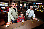 """© Joel Goodman - 07973 332324 . 14/03/2014 . White Horse Pub , Gilda Brook Road , Eccles M30 0DX , UK . Bernadette (centre) with customer Danny """" Jock """" Donnally (58) (left) and customer of 30 years , Frank Kenny (74) (right) (07706 740908) , singing around the piano . Landlady Bernadette """" Babs """" Harvieu (52 , correct) is unable to renew her contract with Robinsons brewery . Photo credit : Joel Goodman"""