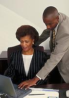 Man and woman conducting business, working on laptop. Professionals. Businesswoman. Businessman. African American. Ethnic. Denver Colorado USA.